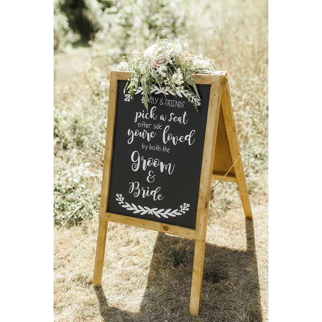Wedding flowers on groom and bride blackboard sign
