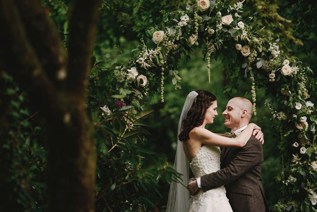 White wedding flower arch with married couple