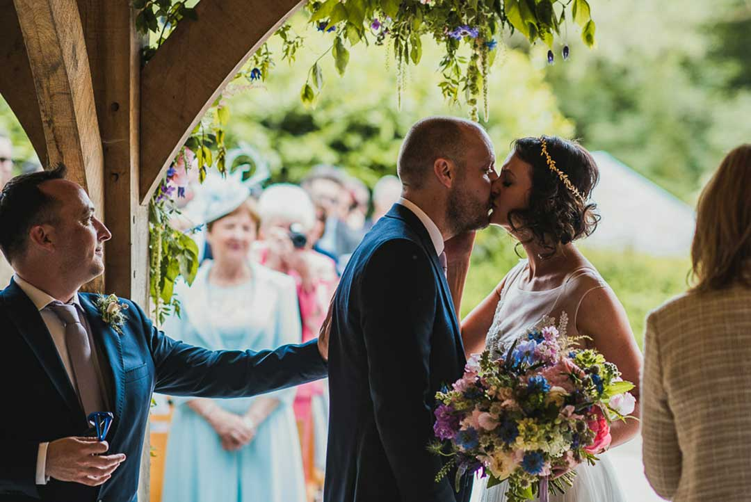 Partial Flower Arches with bride and groom kissing