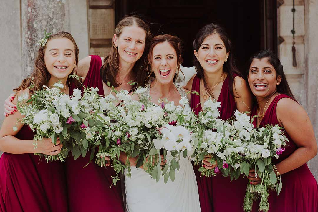 Bride and Bridesmaids smiling with flowers