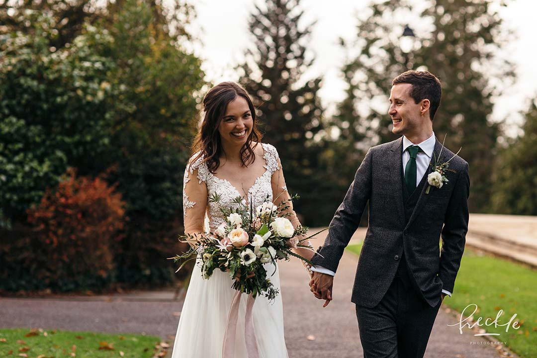Bride and bridegroom holding hands in a garden