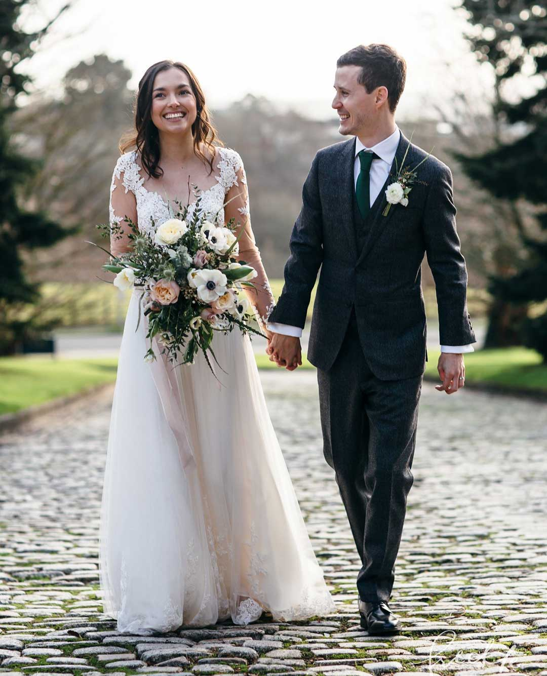 Newly married couple walking in garden