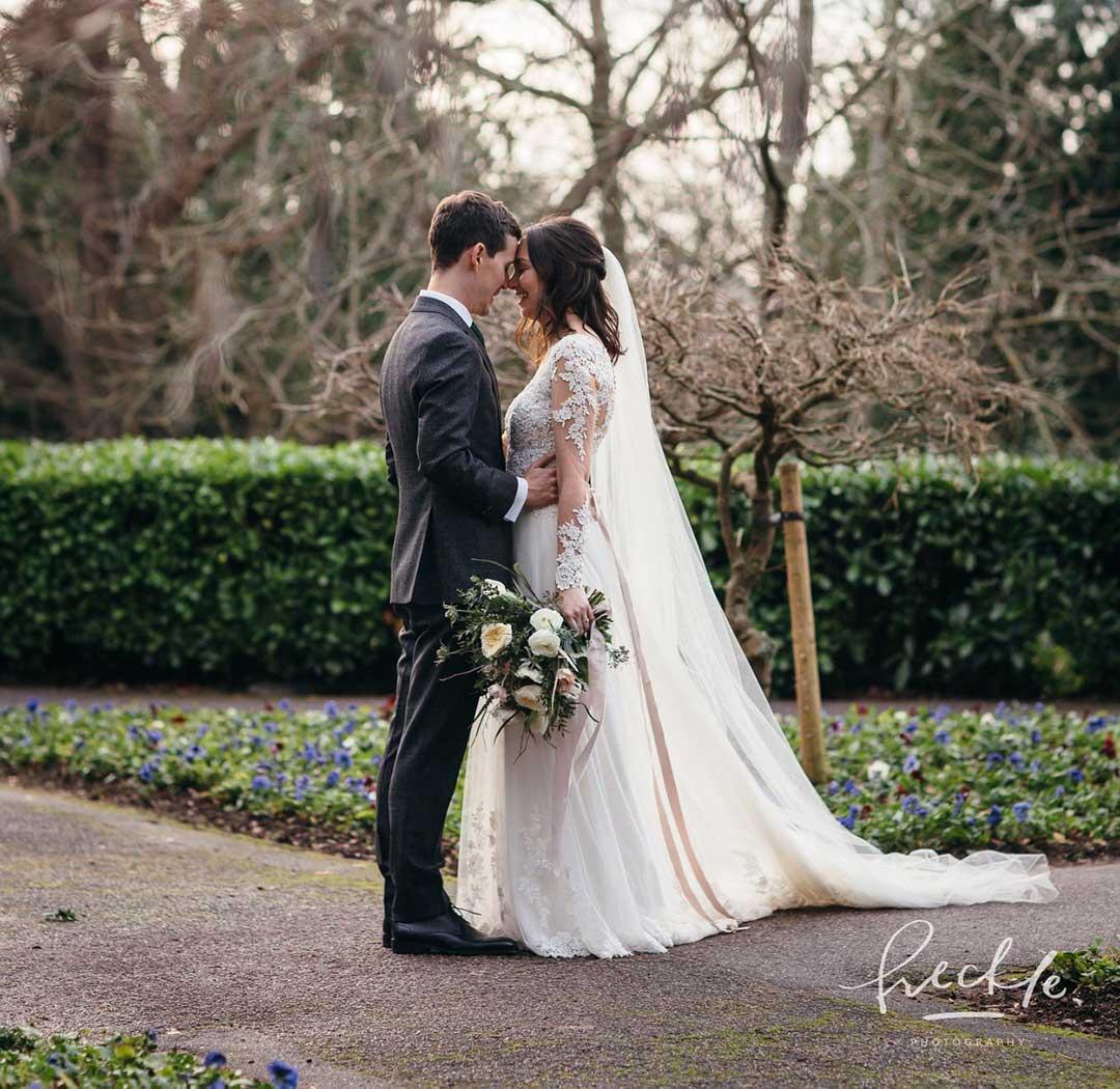 Bridegroom holding bride in garden