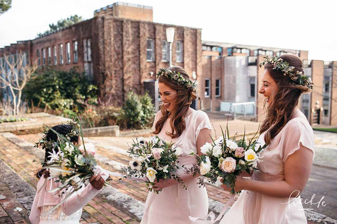 3 bridesmaids in pink dresses holding bouquets