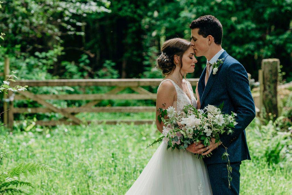 groom holding bride with bouquet