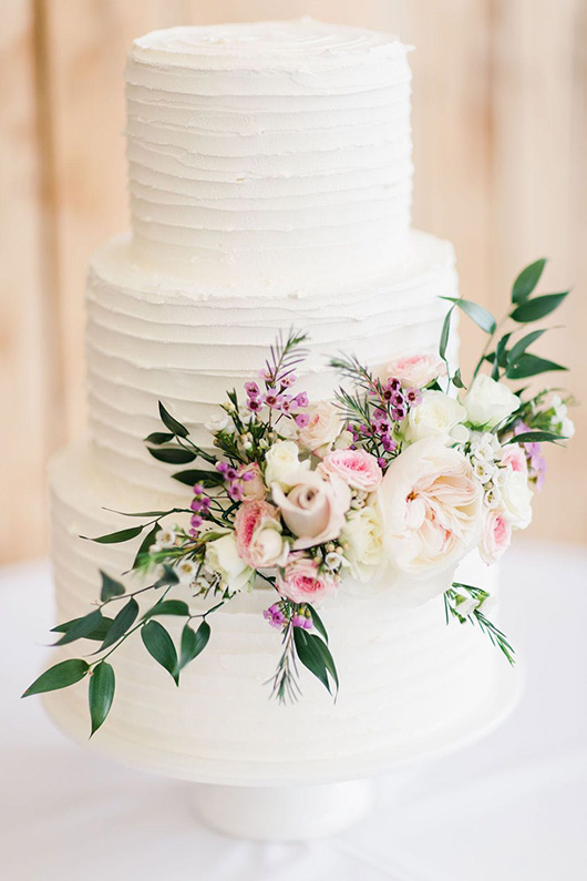 White wedding cake decorated with pink and white flowers