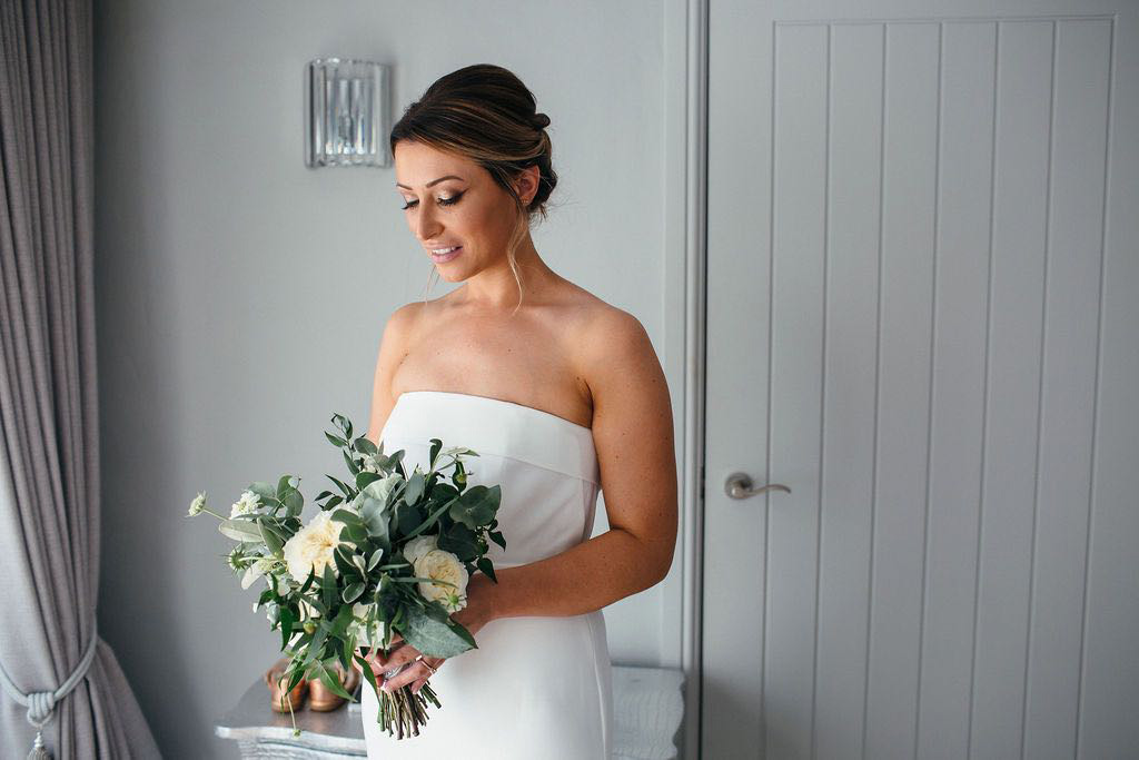 Bride holding green and white bouquet