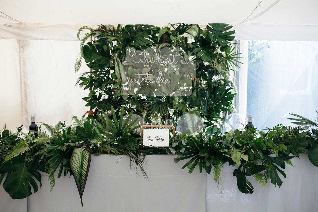Top table decorated with green wedding flowers