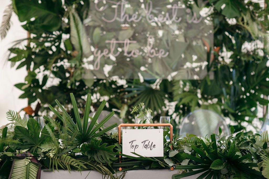 Top table sign decorated with green wedding foliage