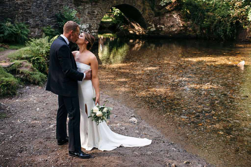Bride and Groom kissing by Devon river