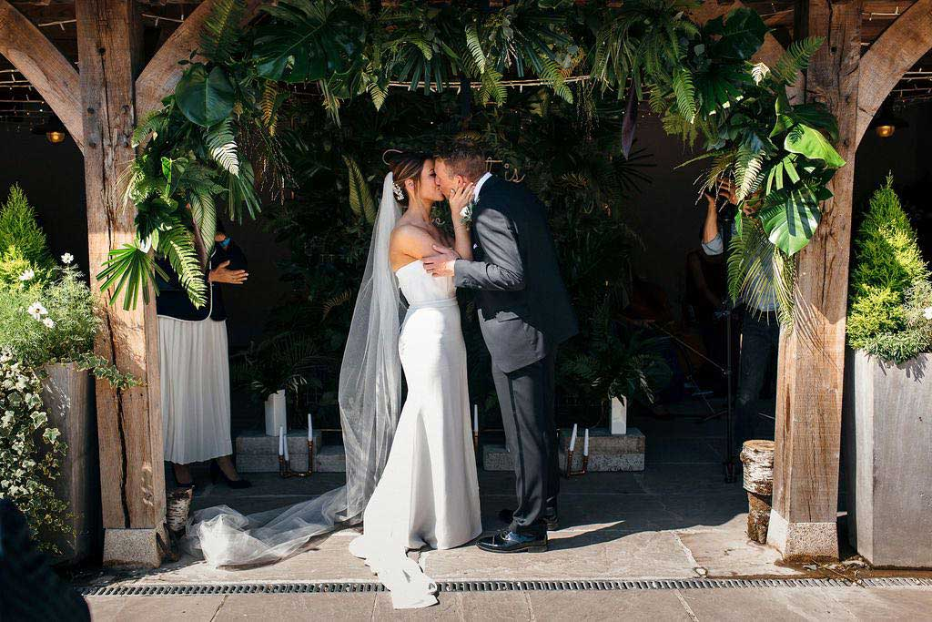 Bride and bridegroom kissing under a wedding bower