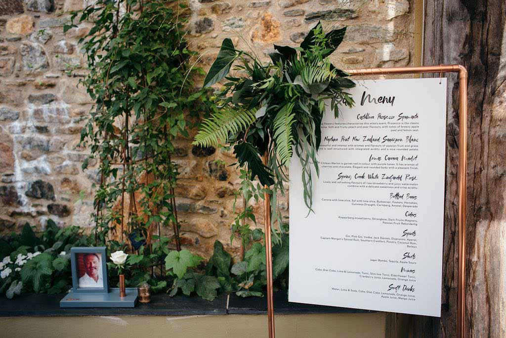 Wedding menu decorated with green foliage