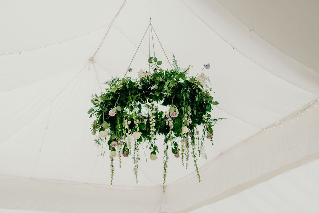 Circular flower decoration hanging from marquee ceiling