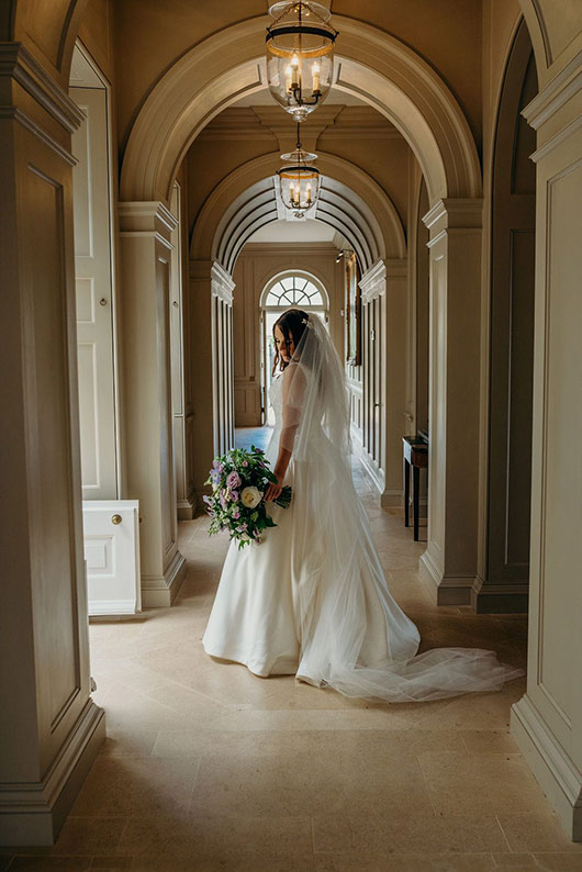 Bride standing in arched corridor holding wedding bouquet