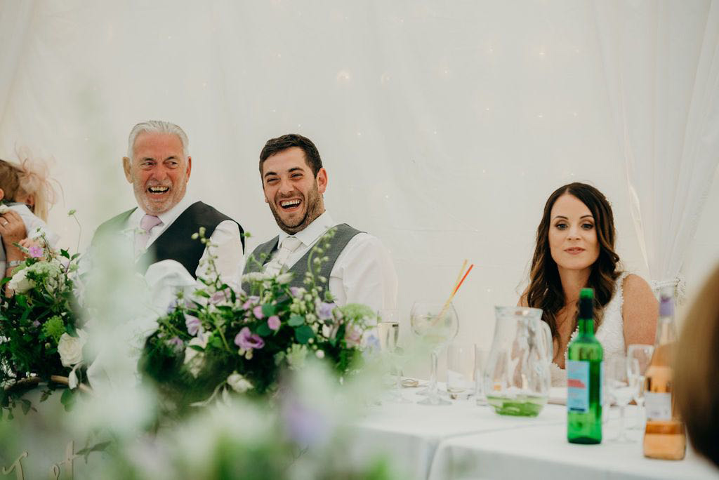 Groom and father laughing during wedding speeches