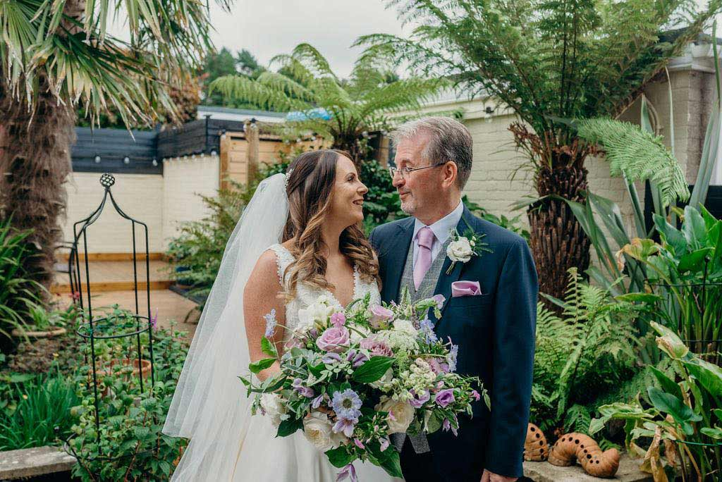 Bride and her father with pink wedding bouquet
