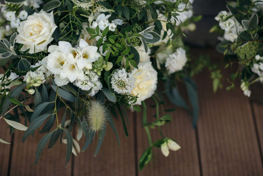 Green and white wedding flowers on decking background