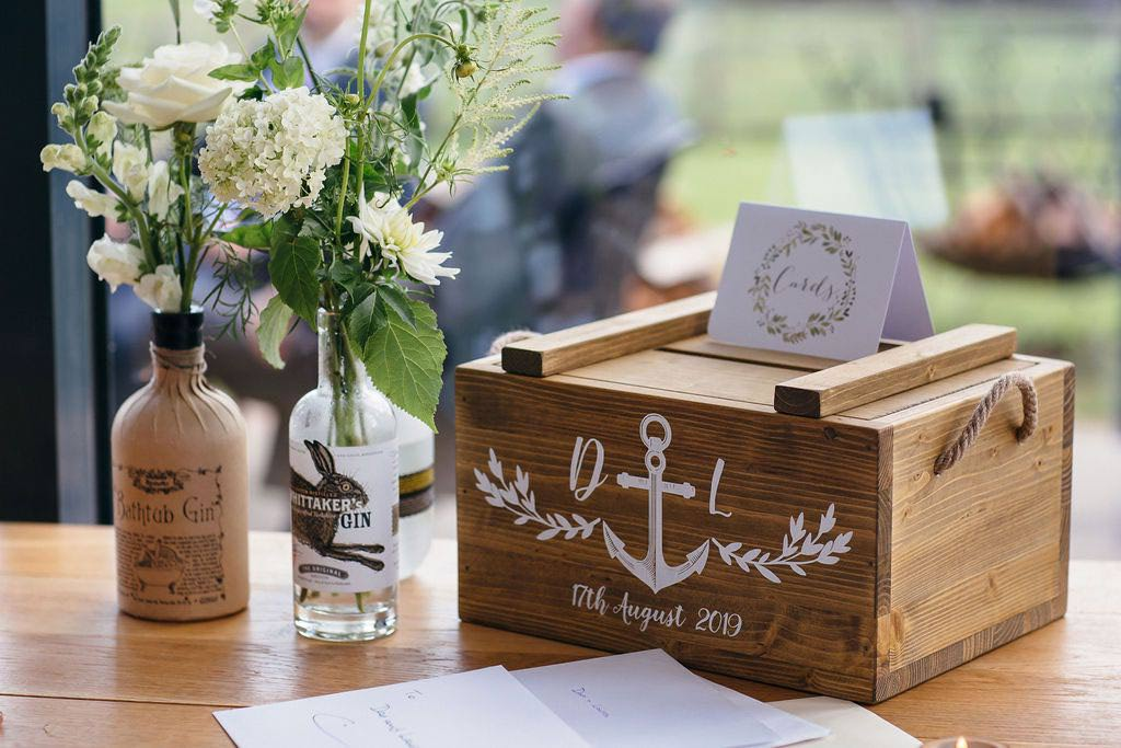 Wooden card box with flowers in old gin bottles
