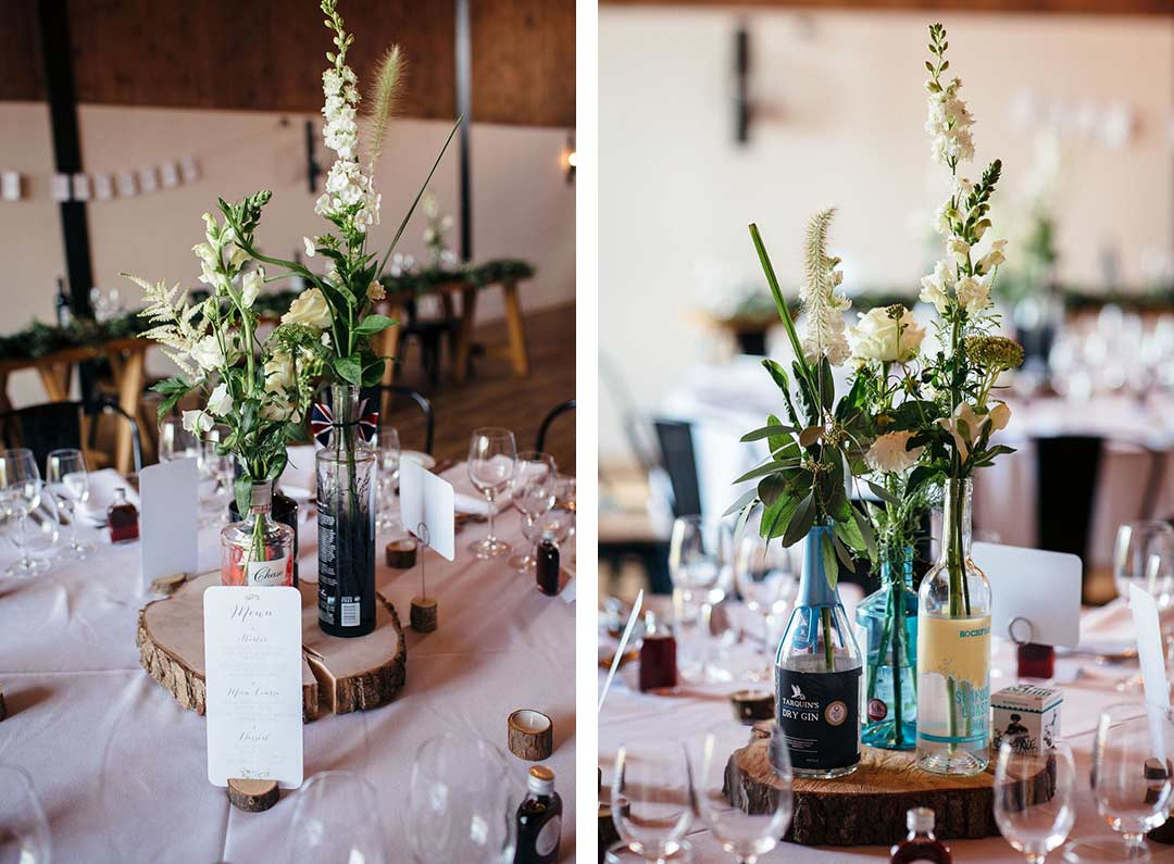 Wedding flowers in old gin bottles decorating reception tables