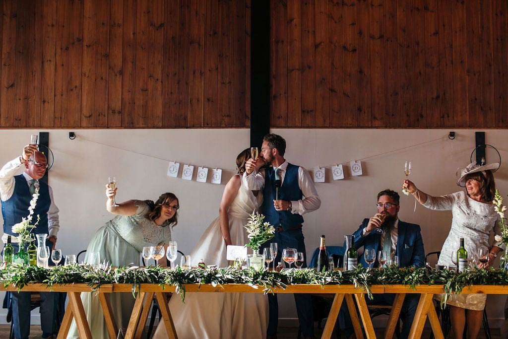 Bride and groom kissing after wedding speech with guest glasses raised in toast