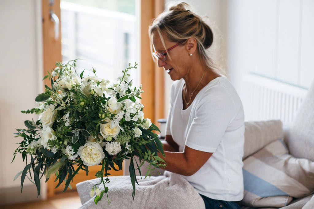 Debbie Morris adding finishing touches to wedding bouquet of green and white flowers