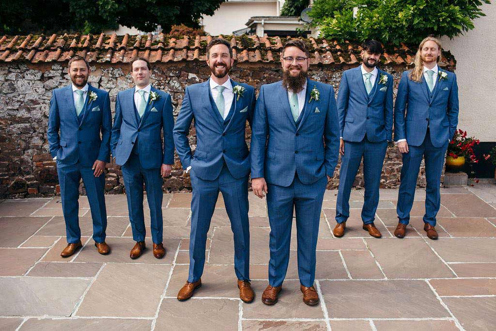 Groom, bestman and ushers wearing wedding buttonholes and blue suits