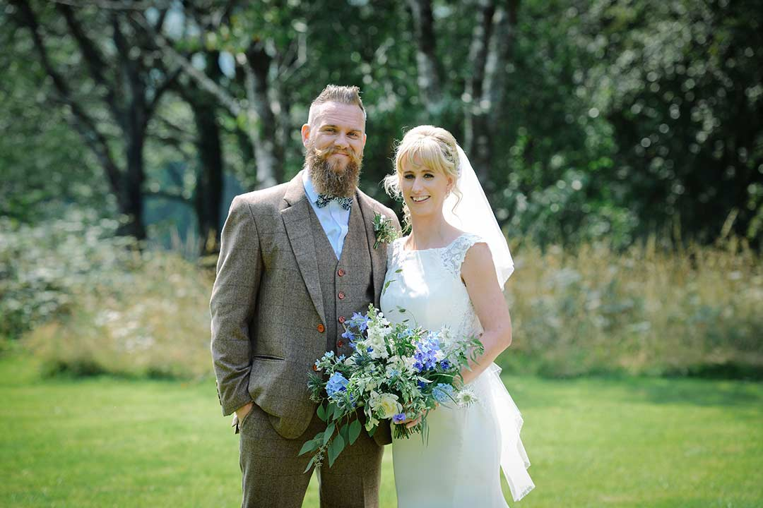 Bride and bridegroom in garden with blue and white bouquet