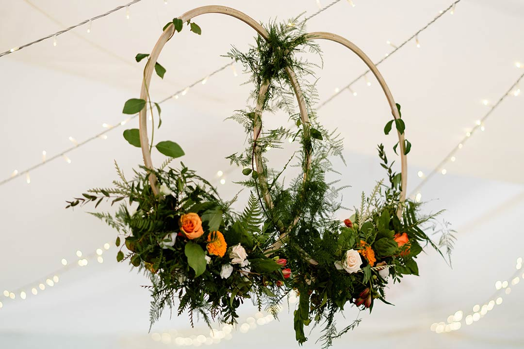 Hoops decorated with flowers below marquee ceiling