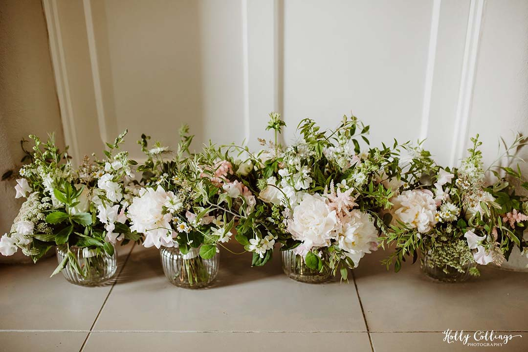 White wedding flowers in vases ready for reception