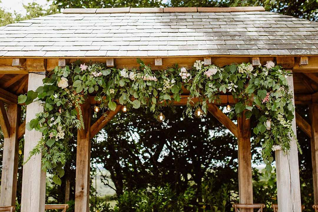White wedding bower decorated with white flowers