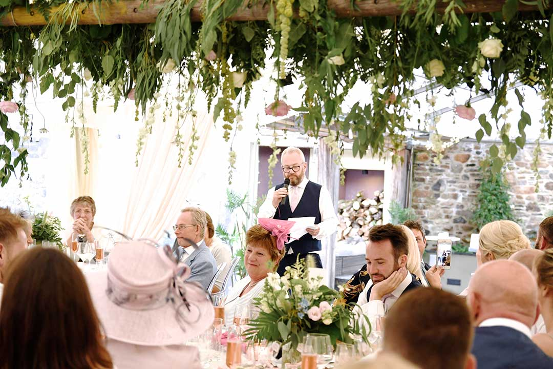 Wedding party under suspended wedding flowers