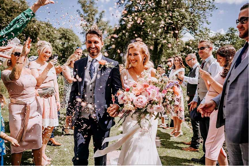 newly married couple showered with confetti
