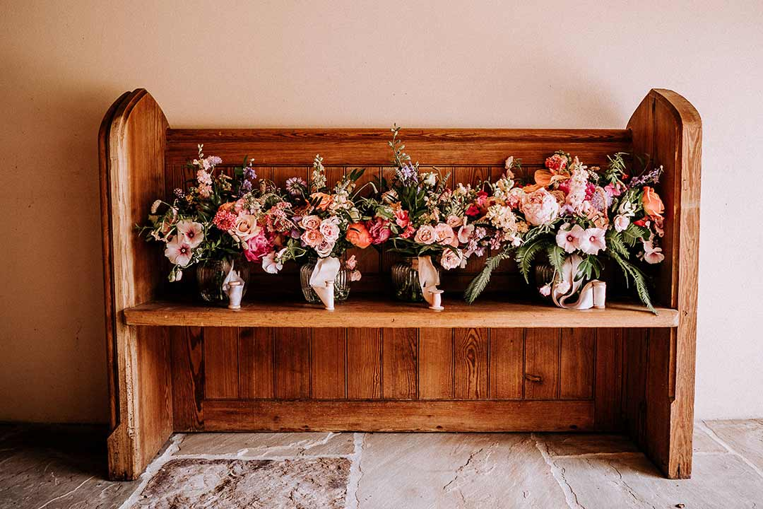 Wedding bouquets arranged on wooden church pew